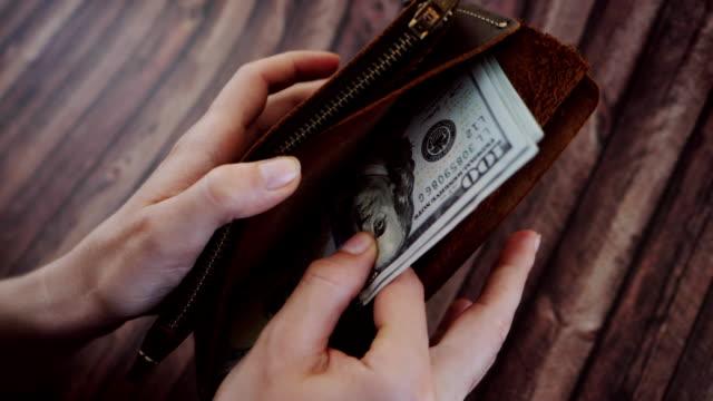 頂視圖的計數的女人,並且把出從她棕色真皮錢包美元。女性擔任錢包木制背景。慢動作 - 銀包 個影片檔及 b 捲影像