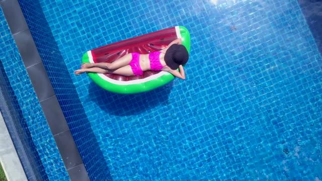 vídeos de stock, filmes e b-roll de vista superior de uma mulher em um terno de biquíni o unicórnio flutuante borrachas. para aproveitar o tempo de relaxamento na piscina de férias no hotel ou resort - flutuando na água