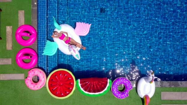 vídeos de stock, filmes e b-roll de vista superior de uma mulher em um terno de biquíni o unicórnio flutuante borrachas. para aproveitar o tempo de relaxamento na piscina de férias no hotel ou resort - inflável