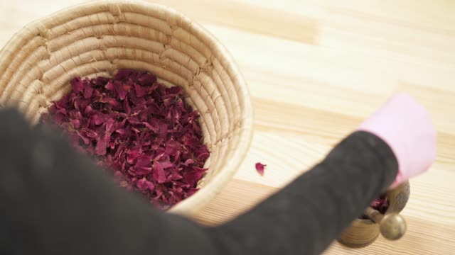 Top view of a woman shifts dried rose petals from a basket to a copper mortar with pestle and grinds it. Top view of a girl shifts dried rose petals from a basket to a copper mortar with pestle and grinds it. mortar and pestle stock videos & royalty-free footage