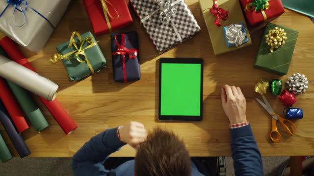 Top View of a Young Man Sitting at His Table Full of Packed Gifts Looking at Green Screened Tablet Computer. Warm Sunlight Covers His Table. Top View of a Young Man Sitting at His Table Full of Packed Gifts Looking at Green Screened Tablet Computer. Warm Sunlight Covers His Table. Shot on RED Cinema Camera in 4K (UHD). table top view stock videos & royalty-free footage