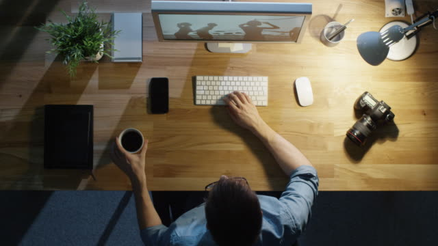 若い写真家処理の平面図写真彼のデスクトップ コンピューターに近付いの後半。彼の机のテーブル ランプが点灯します。彼は、眠気覚ましにコーヒーを飲みます。カメラ、外付けハード ド� - 編集者点の映像素材/bロール