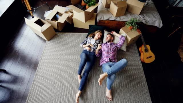 Vue de dessus d'adorable jeune couple allongé sur le sol de leur nouvel appartement dans la chambre, parlant ensuite baisers et des caresses. Lit, guitare, tapis et boîtes en carton sont visibles. - Vidéo