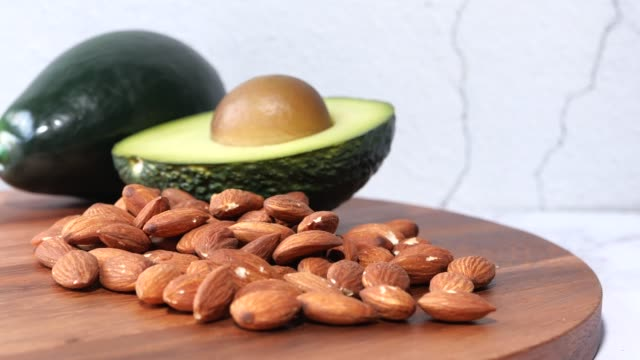top view of almond and avocado on chopping board - articoli casalinghi video stock e b–roll