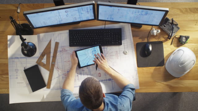 Top View of architectural Engineer Draws on His Blueprints, Compares with Tablet Computer with Green Screen, Using Desktop Computer Also. His Desk is Full of Useful Objects and Evening Sun. video