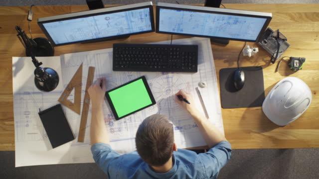 toppvy av arkitekt ingenjör ritar på hans ritningar, jämför med tablet pc med grön skärm, använda stationär dator också. hans skriv bord är full av användbara objekt och evening sun. - man architect computer bildbanksvideor och videomaterial från bakom kulisserna