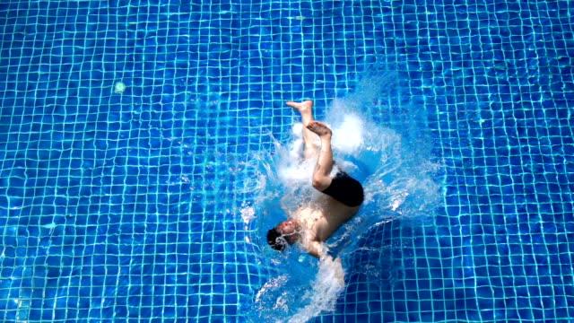 slo mo - top view of asian man trying to do backflip into swimming pool - niedoskonałość filmów i materiałów b-roll