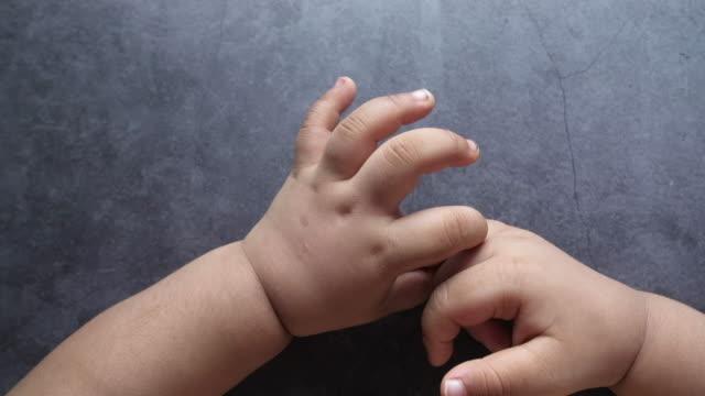 vidéos et rushes de vue supérieure de la main de bébé sur le fond noir. - bras humain
