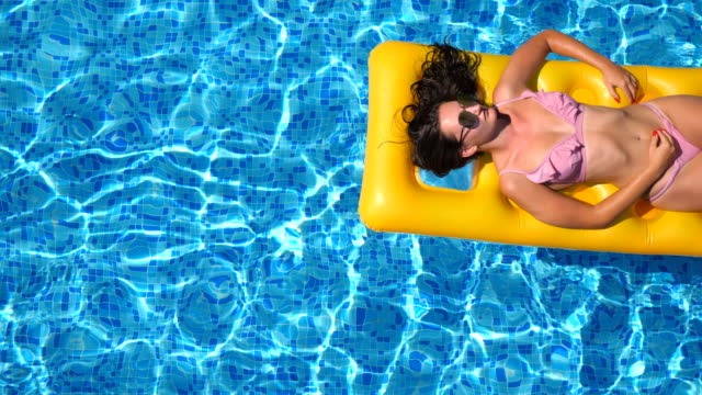 vídeos de stock e filmes b-roll de top view of beautiful tanned girl in sunglasses and pink bikini lying on yellow inflatable mattress in swimming pool. young woman relaxing in basin of hotel during summer travel. concept of vacation. close up - água parada