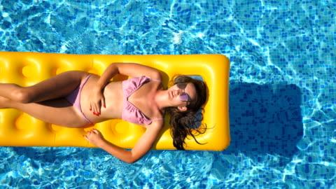 draufsicht der schöne gebräunte mädchen mit sonnenbrille und rosa bikini auf gelben luftmatratze im pool liegen. junge frau im becken des hotels während der sommer-reise entspannend. konzept der urlaub. nahaufnahme - braun stock-videos und b-roll-filmmaterial