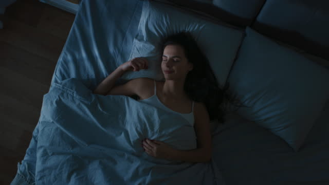 vídeos de stock e filmes b-roll de top view of beautiful young woman sleeping cozily on a bed in his bedroom at night. blue nightly colors with cold weak lamppost light shining through the window. - deitar