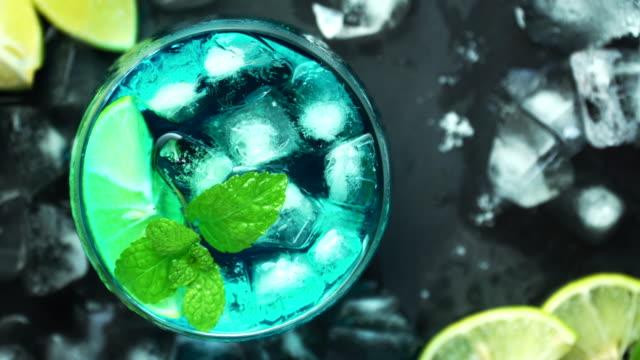 top-ansicht des blauen cocktails auf schwarzem steintisch. cocktail-design-ideen-konzept für werbung. - tropischer cocktail stock-videos und b-roll-filmmaterial