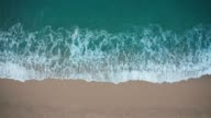istock Top view of blue waves crashing against sand beach 1164014968