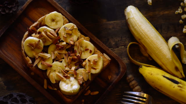 Top view of breakfast, Banana and peanut butter served with bread toasted on wooden table.