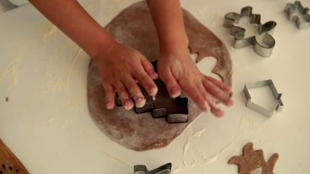 伝統的なクリスマスクッキーを作る子供の手のトップビュー。白いテーブルの上に休日のクッキーのための生の生地とカッター - モミの木の形をしたクッキーを作る - 十二月点の映像素材/bロール