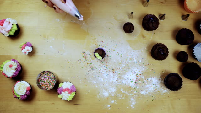 Top view of chocolate cupcakes on the table. Young woman decorating muffins with colored cream from pastry bag video