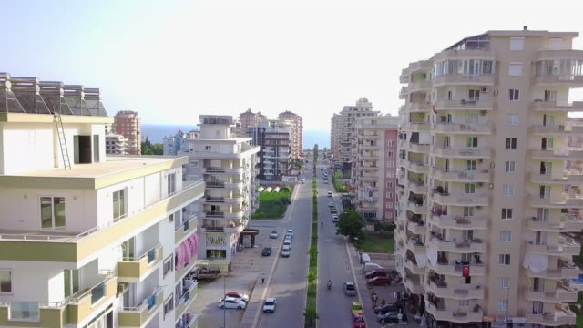 Top view of city road leading to sea. Clip. Road passing among high-rise buildings of city leads to sea on horizon. Top view of straight road among hotels of resort town by sea video