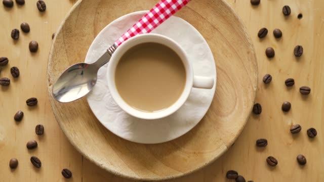 top utsikt över kaffe med sked på dekorativa plattan på träbord - tefat bildbanksvideor och videomaterial från bakom kulisserna