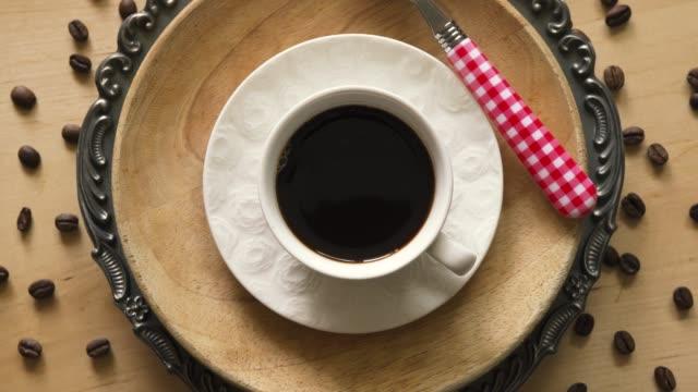 木製テーブルの装飾プレートにスプーン付きコーヒーのトップビュー - ソーサー点の映像素材/bロール