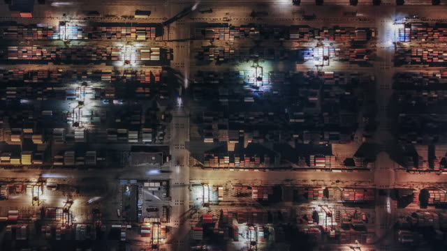 T/L PAN Top View of Container Terminal at Night Rows of Shipping Containers in Port Terminal at Night warehouse aerial stock videos & royalty-free footage