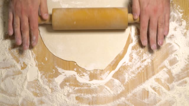 Top view of cook rolling dough with rolling pin video