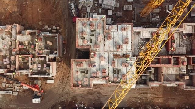 建設現場でのクレーンブームと建設労働者のトップビュー - クレーン点の映像素材/bロール