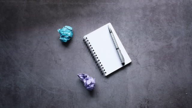 Top view of crumpled paper balls and notepad on gray background