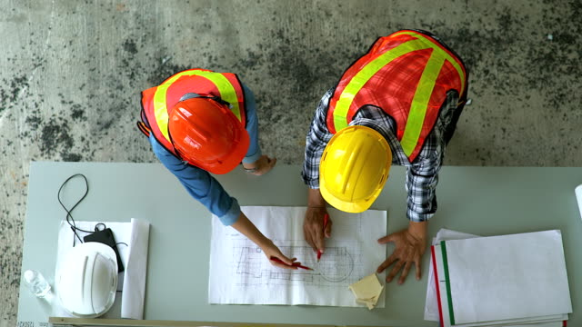 top view of engineer and site manager looking at paper blueprint plans at a construction site. business concept for the teamwork of heavy industry. - architect stock videos and b-roll footage