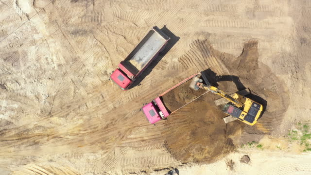 Top view of excavator pouring sand in dump truck. Mining industry Top view of excavator pouring sand in dump truck. Mining industry crane construction machinery stock videos & royalty-free footage