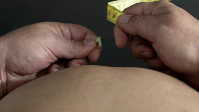 Top view of fat man with big beer belly measuring waistline, weight control video