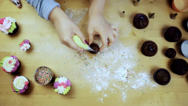 Top view of female hands decorating the chocolate cupcakes. Young woman using the pastry bag for cream video