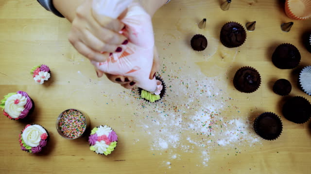 Top view of female hands decorating the chocolate cupcakes. Young woman using the pastry bag for colored cream video