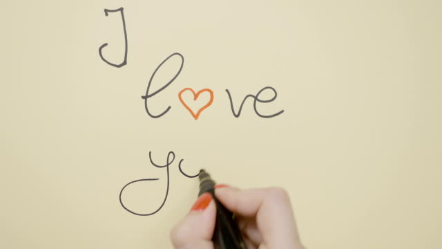 Top view of female hands writing I love you using a red and black marker on a greeting card and drawing a heart video