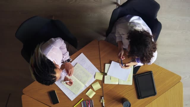 Top view of females hands writing notes in notepad. Writing down business ideas. Closeup of two business woman discussing ideas. Unrecognizable women in white blouses sitting at the wooden table