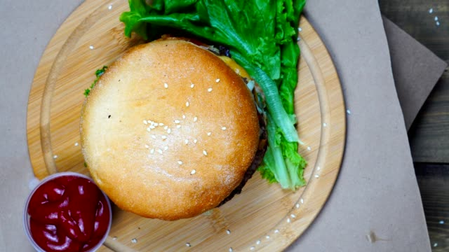 Top view of fresh appetizing hamburger rotating on wooden plate