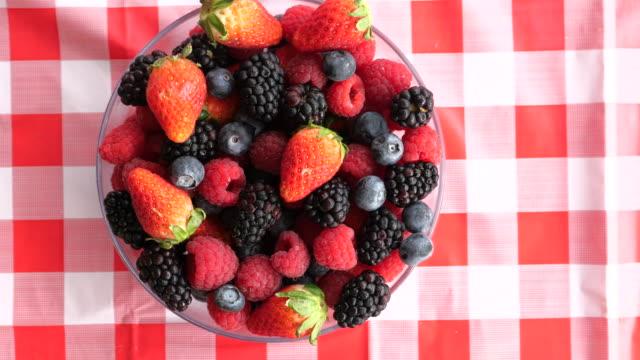 vídeos de stock e filmes b-roll de top view of fresh berry fruits in a bowl - saladeira