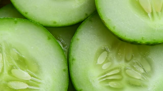 top view of fresh sliced cucumber rotation - cetriolo video stock e b–roll