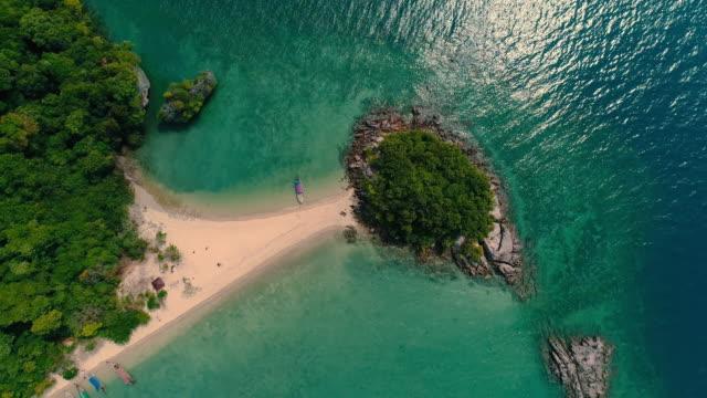 aerial. top view of green island and beach with traditional thai boat at the sunset. - spektakularny krajobraz filmów i materiałów b-roll