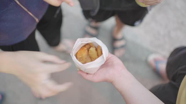 vídeos de stock, filmes e b-roll de vista superior das mãos colhendo frito de banana frita em saco de papel. comida de rua tailandesa. - comida salgada