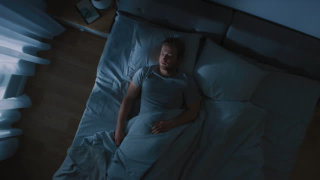 vídeos de stock e filmes b-roll de top view of handsome young man sleeping cozily on a bed in his bedroom at night. blue nightly colors with cold weak lamppost light shining through the window. - deitar
