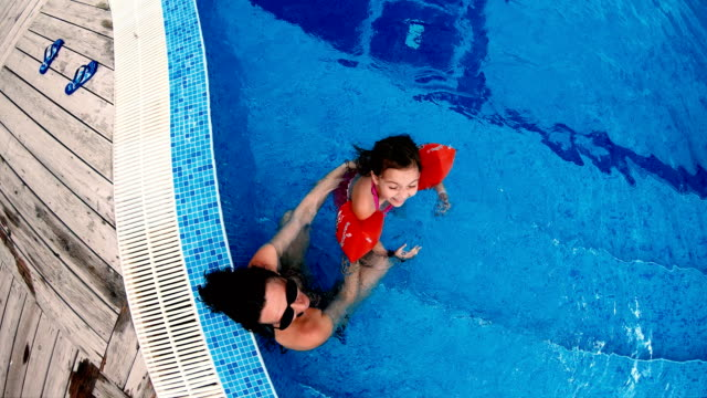 Top view of happy family, mother and daughter with arm bands smiling and splashing water to camera, slow motion