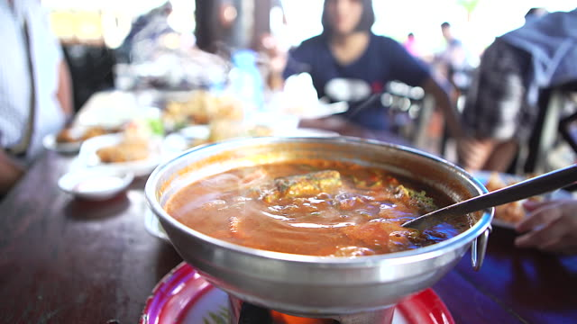 Top view of hot & spicy thai curry,sour soup vegetable and Thai's herbs, Thai famous style served in hot pot at the restaurant. video
