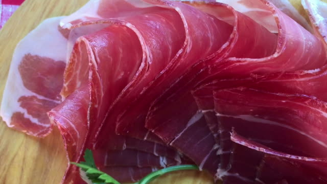 Top view of jamon slices, close up view zoom out. Prosciutto thinly sliced and served uncooked. video