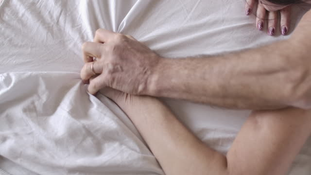 Top view of male Caucasian senior hand taking female palm squeezing bed sheets. Unrecognizable mature couple in love having sex in bedroom in the morning. Love, enjoyment. Cinema 4k ProRes HQ. Top view of male Caucasian senior hand taking female palm squeezing bed sheets. Unrecognizable mature couple in love having sex in bedroom in the morning. Love, enjoyment. Cinema 4k ProRes HQ. falling in love stock videos & royalty-free footage