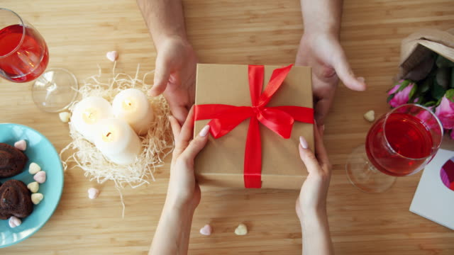 Top view of male hands giving gift box to female hands in cafe on St Valentine's day