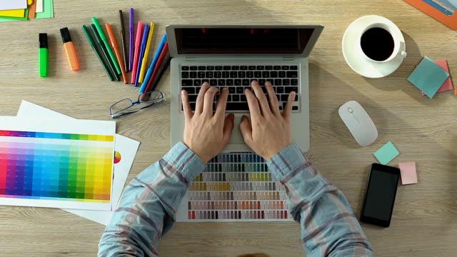draufsicht der männlichen web designer arbeiten am laptop im büro, kreativität, freiberuflich - reisebüro stock-videos und b-roll-filmmaterial