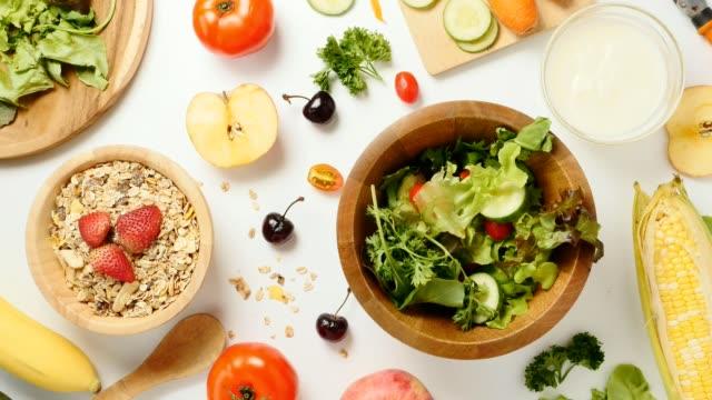 vidéos et rushes de vue du dessus de la salade de crudités, muesli et fruits frais sur fond blanc. arrêter le mouvement - fibre
