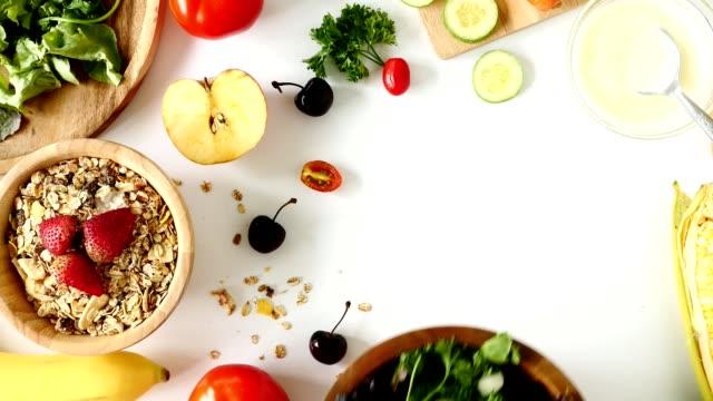 vidéos et rushes de vue de dessus de la salade de crudités, muesli et fruits frais sur fond blanc - fibre