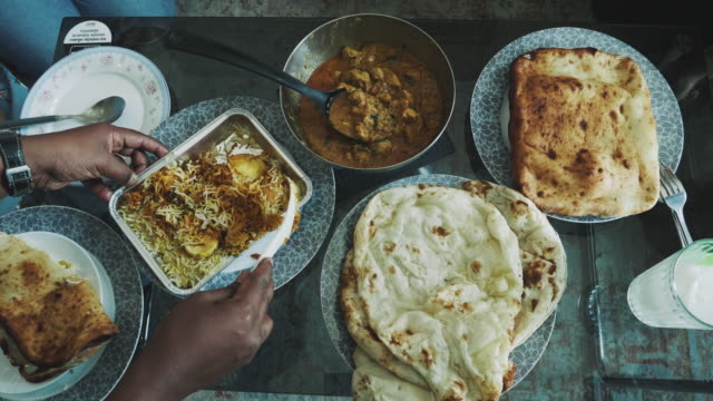 Top view of people and Variety of Indian Food served on a Dining Table - Stock video video