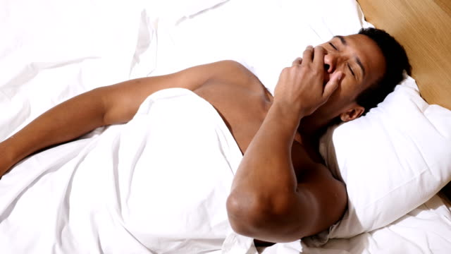 Top View of Relaxed African Man Awakes from Sleep in Morning video